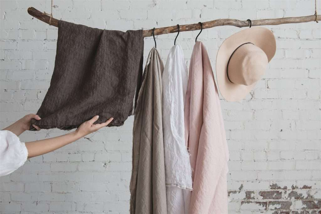linen fabric hanging on a branch with hat